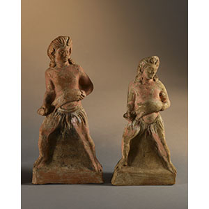 Two statuettes depicting two young satyrs holding a wineskin